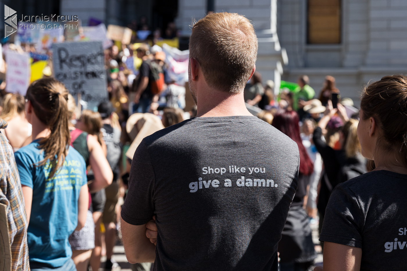 "Coloradoan's shirt reads ""Shop like you give a damn."" at climate rally"