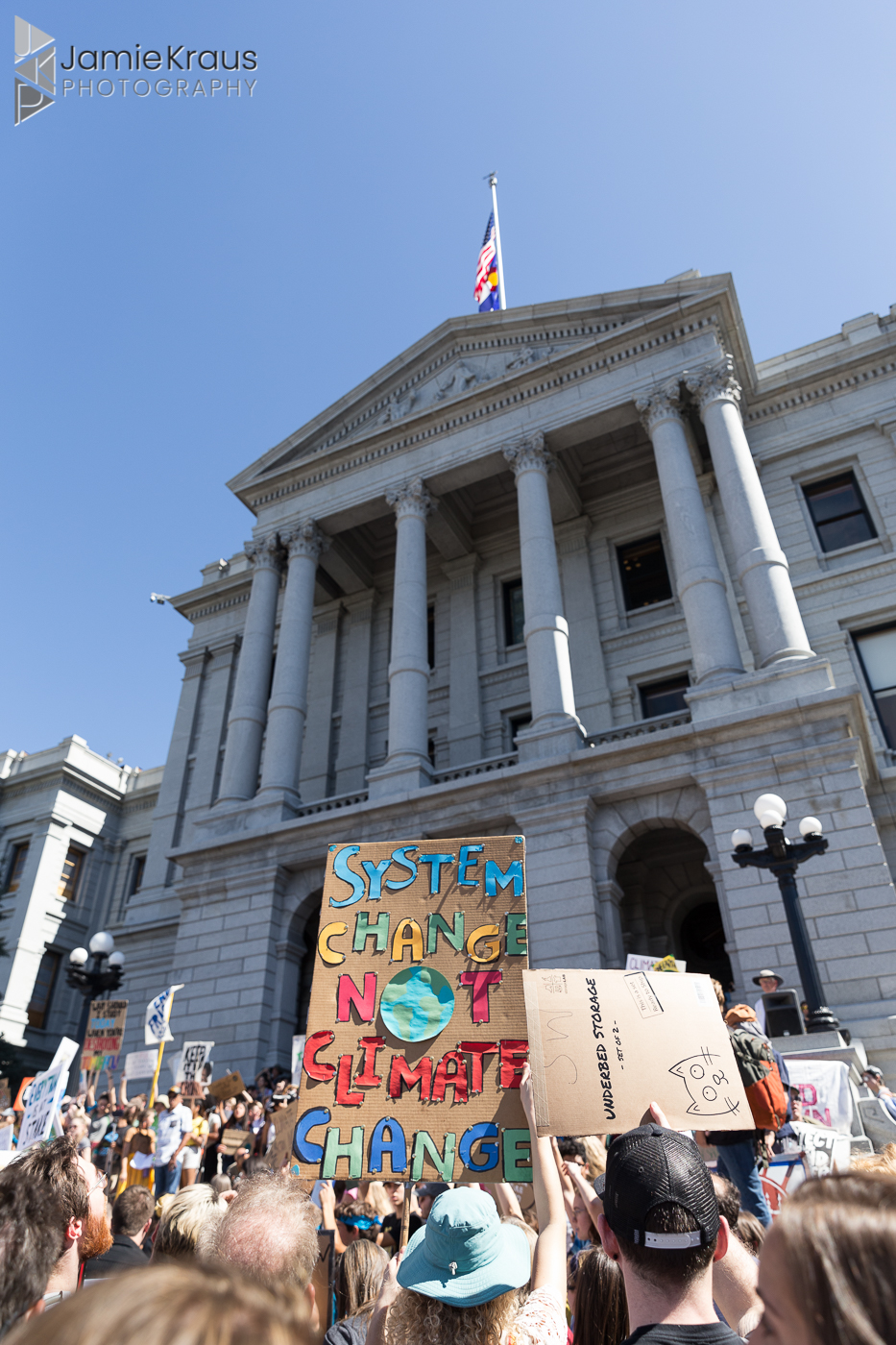 "Sign reading"" System Change not Climate Change"" in front of Colorado Capitol Building"