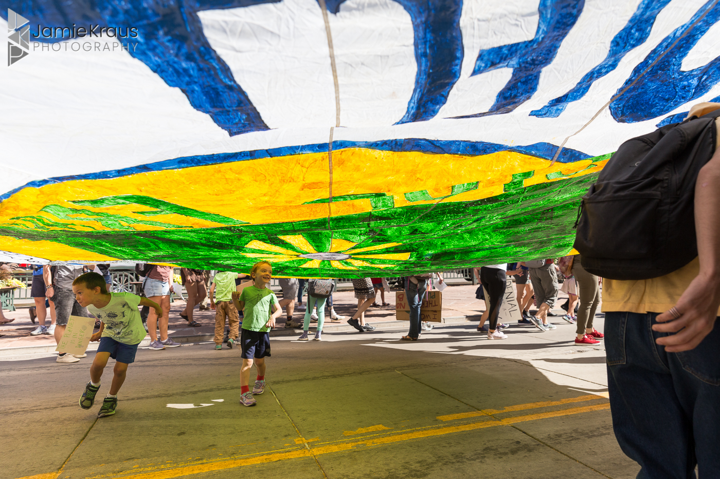children play under climate protest parachute in Denver
